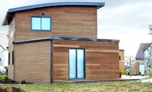 Maison à ossature bois avec toiture en zinc noir et bardage en Red Cédar